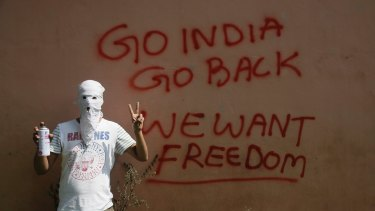 A masked Kashmiri protester in front of graffiti on the wall of a building in Srinagar.