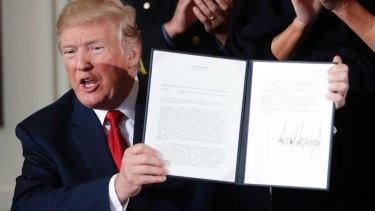 US President Donald Trump displays his presidential memorandum declaring the opioid crisis a public health emergency.