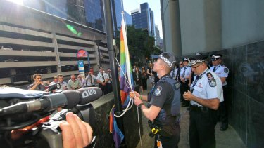Transgender police officer Mairead Devlin raises the rainbow flag for the first time outside QPS headquarters.