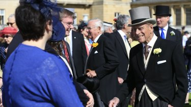 Prince Philip, right, speaks to guests during a garden party in the grounds of Buckingham Palace.