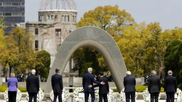 US Secretary of State John Kerry, fourth from left, puts his arm around Japanese Foreign Minister Fumio Kishida after G7 foreign ministers laid wreaths at Hiroshima Peace Memorial Park last month. The bombed movie theatre is seen in the background.