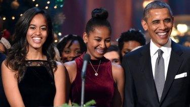 Malia and Sasha Obama with their father in Washington at Christmas,  2014.