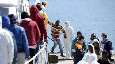 Migrants disembark from an earlier Italian Coast Guard boat at Palermo.