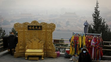 A vendor wearing a protective face mask waits for customers at the Jingshan Park in Beijing.
