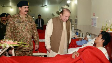 High level: Pakistani Prime Minister Nawaz Sharif and army chief Raheel Sharif visit a student injured in the Peshawar school massacre.