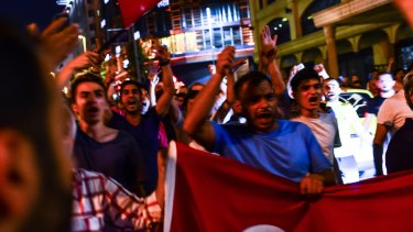 Supporters of Turkish President Recep Tayyip Erdogan march in the main streets of Istanbul, in the early morning hours of Saturday.
