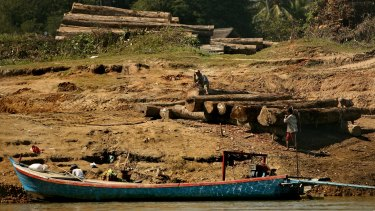Men working with logs on the banks of the Irrawaddy River between Bhamo and Shwegu in Kachin state, Myanmar.