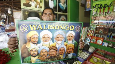 A vendor of merchandise at the shrine with a poster of the Wali Songo, or nine saints, credited with bringing Islam to Java.