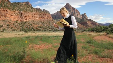 Sophia Hewson reads to mountains called the Court of the Patriarchs in Utah as research for her exhibition.