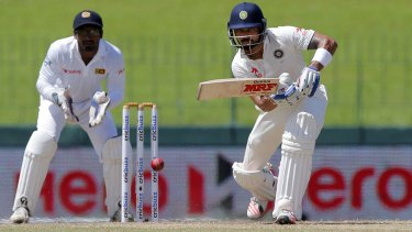 India's captain Virat Kohli lunges forward at a delivery as Sri Lanka's wicket keeper Kusal Janith Perera watches.