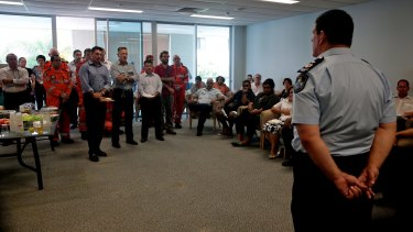 Police and emergency services personnel meet on Monday in the aftermath of the killing of eight children in Cairns.