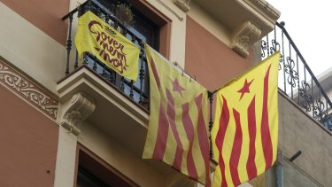 Pro-independent Catalonia flags hang from the balcony of a home in Barcelona on Monday.