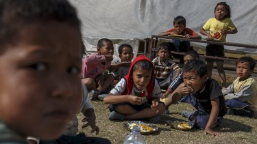 Earthquake survivors eat breakfast in a makeshift shelter in Sankhu, on the outskirts of Kathmandu, on Tuesday.
