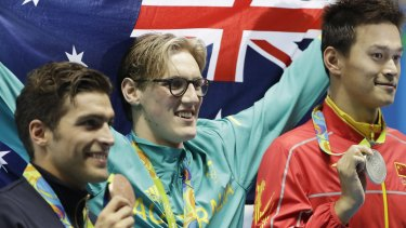 Mack Horton, centre, celebrates after beating Sun Yang, right. in the the men's 400m freestyle.