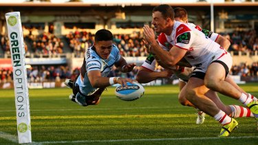 Lovely stuff: Valentine Holmes flies over for a try to Cronulla.