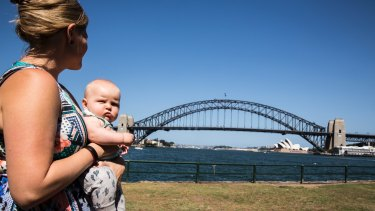 Claudia Tyson holds a friend's baby at Blues Point Reserve, which will be affected by excavation for the Sydney Metro.