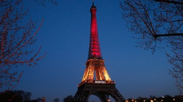 The Eiffel tower illuminated with the Belgium national colours black, yellow and red.