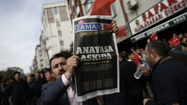 "A man holds Saturday's copy of the newspaper which reads ""the constitution suspended"" as people gathered in support outside the headquarters of Zaman newspaper in Istanbul, on Sunday."