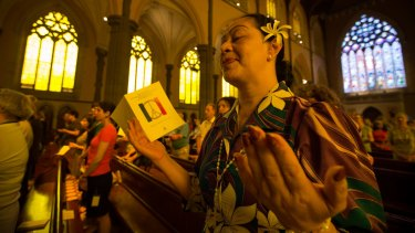 A woman prays at a mass at Melbourne's St Patrick's Cathedral in memory of the dead and wounded in Friday's Paris attacks.