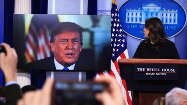 Donald Trump speaks via a video to journalists at a press briefing at the White House with press secretary Sarah Sanders at the lectern.