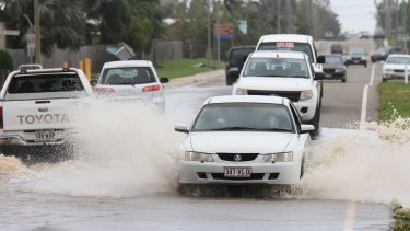 Cars drive through partially flooded roads in Bowen the day after Cyclone Debbie blew through.