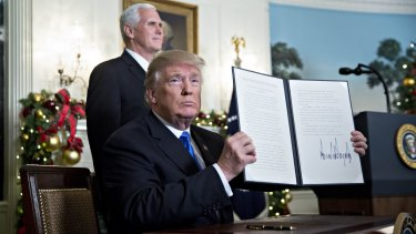 US President Donald Trump holds up the proclamation on Jerusalem next to Vice President Mike Pence last week.
