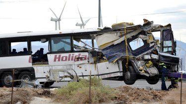 Workers prepare to haul away the tour bus that crashed, leaving several tourists dead.