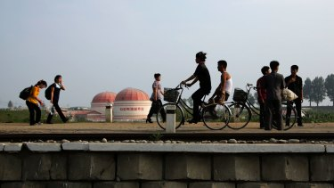 """People walk and cycle past a factory dome with writing which reads """"First priority: self-development"""" in Hamhung, North Korea, on Thursday."""
