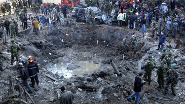 Rescue workers stand around a massive crater after a bomb attack that  killed Lebanese leader  Rafiq Hariri in Beirut on February 14, 2005.