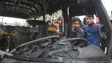 People inspect the scene after a car bomb explosion at a crowded outdoor market in the Iraqi capital's eastern district of Sadr on Monday.