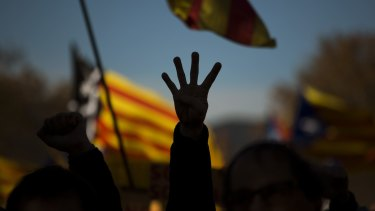 A pro independence demonstrator holds up four fingers symbolising the four bars of the Catalonian flag.