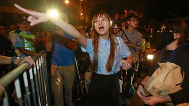 Newly elected Hong Kong lawmaker Yau Wai-ching shouts at police officers as thousands of people march in a Hong Kong street.