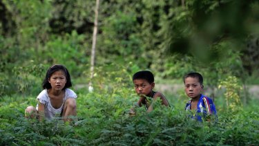 North Korean children look up from the side of a road near Hamhung on Thursday.