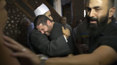 The Imam of al Thawrah Mosque, Samir Abdel Bary, gives condolences to film director Osman Abu Laban, centre, who lost four relatives in the EgyptAir plane crash, at al Thawrah Mosque in Cairo.