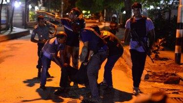 An injured man receives help after an attack at a Dhaka restaurant.