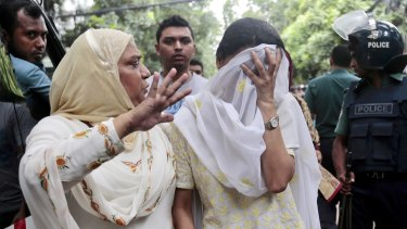 A relative tries to console Semin Rahman, covering face, whose son is missing after militants took hostages in a Dhaka cafe.