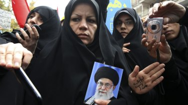 An Iranian demonstrator holds a portrait of the Supreme Leader Ayatollah Ali Khamenei, as another shows her hand with a slogan in support of the leader last month.