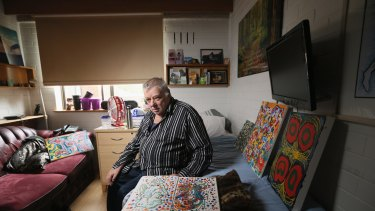 Sambell Lodge resident Graeme Doyle in his room, surrounded by his artwork.