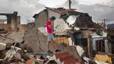 A man talks on his phone while searching for belongings amid the rubble of his home destroyed by Hurricane Matthew in Baracoa, Cuba.