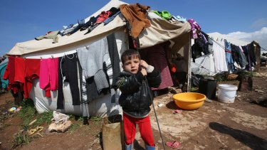 A Syrian refugee boy stands outside his tent pitched amid olive orchards in the northern Syrian province of Idlib in 2013 when the growing refugee population numbered 16,000.