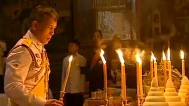 Thailand's new King Maha Vajiralongkorn Bodindradebayavarangkun lights candles for his father at the Grand Palace in December.