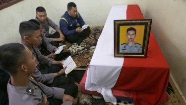 Police officers pray near the coffin of their slain colleague on Thursday.