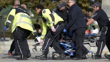 Paramedics and police pull a victim away from the Canadian War Memorial in Ottawa