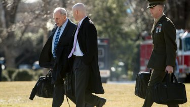 White House Chief of Staff John Kelly, left, and Director of Legislative Affairs Marc Short, centre, prepare to join Donald Turmp aboard Marine One for Camp David.