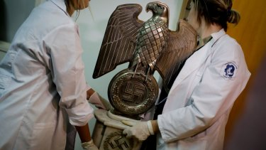 Members of Argentinian federal police carry a Nazi statue found hidden in a house in Buenos Aires.
