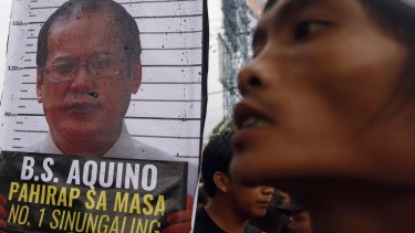 A placard containing an image of Aquino near a protester after demonstrators were blocked from marching towards Batasang Pambansa, where Aquino addressed the nation.