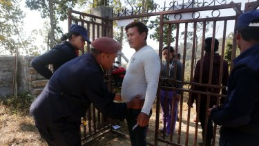 A Nepalese policeman checks a man for weapons during the legislative elections in Chautara, Nepal, on Sunday.