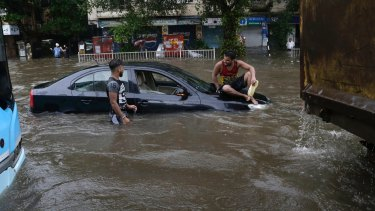 A man sits on a car that got stuck in a waterlogged street following heavy rains in Mumbai.