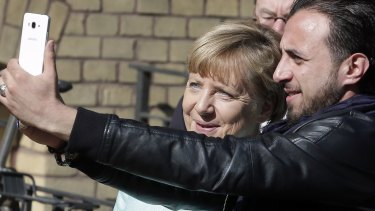 An unidentified man takes a picture of himself and German Chancellor Angela Merkel, left, during Merkel's visit to a registration centre for migrants and refugees in Berlin.