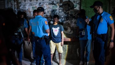 Police question a man during a night patrol at a shanty community on in Manila on the weekend.